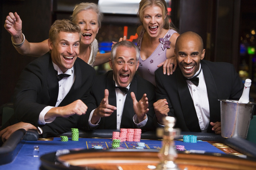 Group of friends celebrating at roulette table in casino