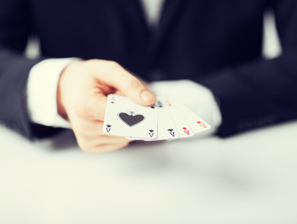 man hand showing four aces